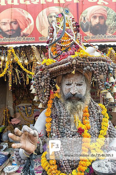 White ash covered sadhu with a hat decorated with Marigold garland necklaces and pearls  For editorial use only  Allahabad Kumbh Mela  World's largest religious gathering  Uttar Pradesh  India.