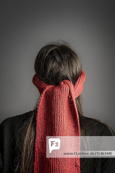 Girl with dark long hair blindfolded with a red knitted scarf- back view.
