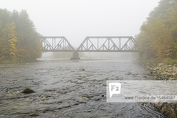 Railroad bridge at the East Branch of the Pemigewasset River crossing along the old Boston & Maine Railroads Pemigewasset Valley Railroad in North Woodstock  New Hampshire on a foggy autumn day.