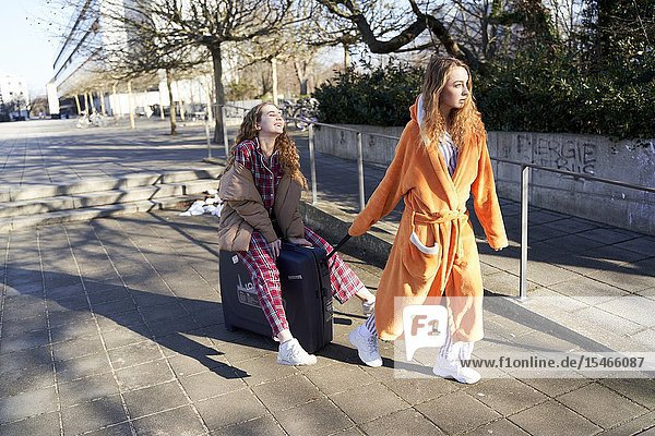 Two young sleepy women in pyjama and bathrobe at university campus with trolley case