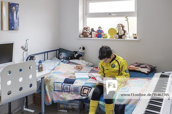 England  Uk-Young boy  11 years in Little league football outfit reads a book in his bedroom.
