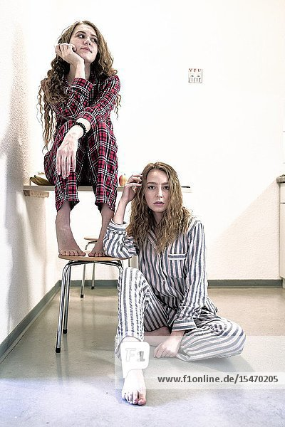 Two young women wearing pyjamas at home