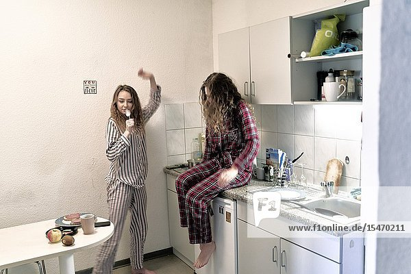 Woman singing with spoon as microphone in kitchen  wearing pyjama