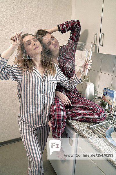 Two young women behind plastic foil in kitchen  wearing pyjamas