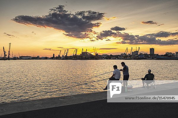 Anglers against the setting sun in the Port of Burgas  Bourgas  Bulgaria.