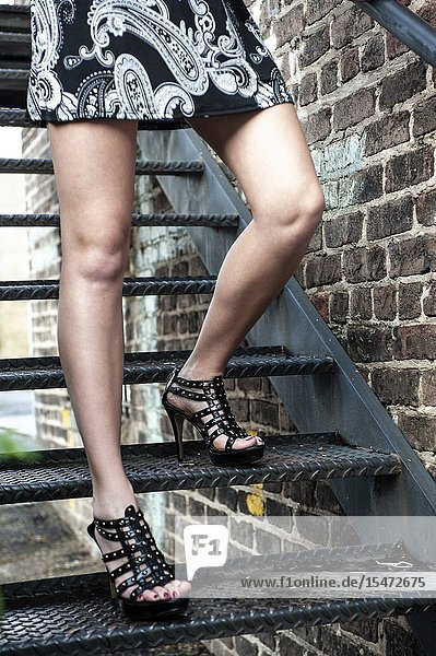 Partial view of a woman's bare legs walking down a metal stairway outdoors.