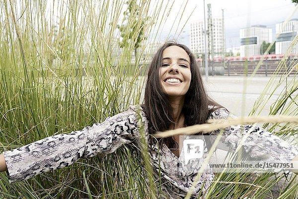 Happy woman between nature grass in city