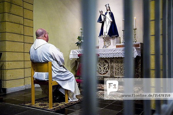 Hulsberg  Netherlands. Catholic priest  father and pastor praying the rosary in front of a Mother Mary Statue inside his rural  village church.