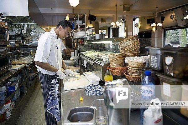 Rotterdam  Netherlands. Chef and culinary cook preparing a lunch inside the professional  restaurant kitchen of Wester Paviljoen on Nieuwe Binnenweg.
