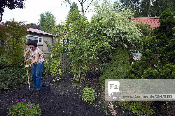 Tilburg  Netherlands. Senior adult woman working in the garden at her rural garden shed inside the grounds of 'Tot Nut en Genoegen'.