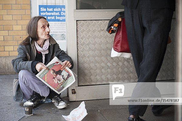 Berlin  Germany. Homeless and impoverished mature adult woman sitting down on the pavement at Ostbahnhof  trying to sell a newspaper and magazine  helping her to earn a small living.