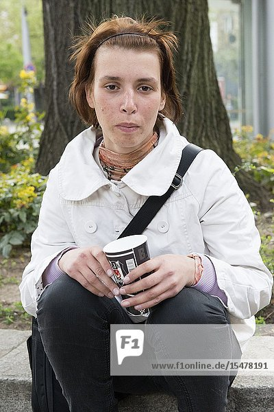 Sofia  Bulgaria. impoverished  young adult Roma woman begging for money in the streets of the Bulgarian capitol  using a carton  disposable coffee cup.