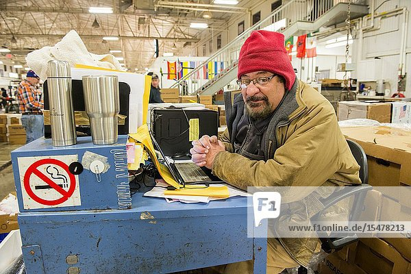 New York City  USA. Wholesale market stall employee waiting to crunch numbers after preparing orders for customers at the New Fulton Fish Market  Hunts Point  The Bronx.