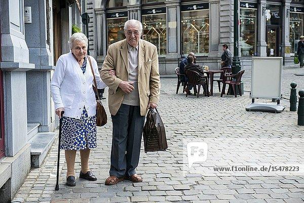 Brussels  Belgium. Elder  retired couple walking their neighborhood towards the super market for groceries..