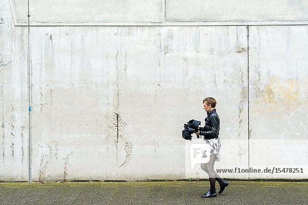 Rotterdam  Netherlands. Young caucasian woman walking by an old  concrete factory wall in Katendrecht neighborhood  while folding up her umbrella after ea shower of rain.