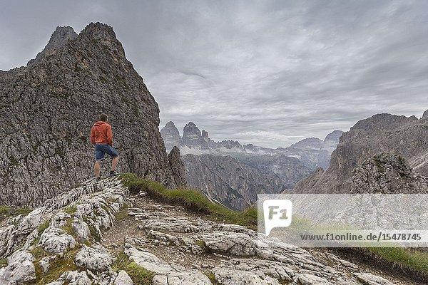 Hiker admires Tre Cime di Lavaredo  Belluno  Veneto  Italy.