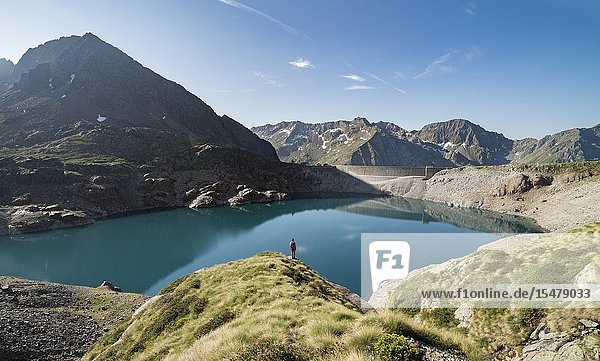 Hiker looks at dam from shores of Lake Baitone  Val Malga  Adamello Regional Park  province of Brescia  Lombardy  Italy.