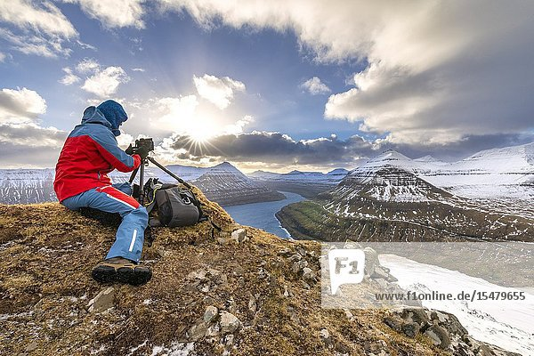 Photographer take a picture from a mountain near the villages of Funningur and Gjogv (Eysturoy island  Faroe Islands  Denmark) (MR).