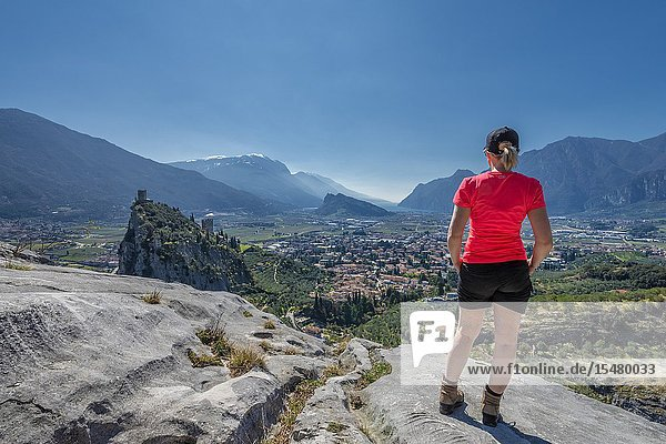 Arco  Trento province  Trentino  Italy  Europe. A Woman admires the panorama of the mountain Colodri  the view extends over the city of Arco to the Lake Garda.