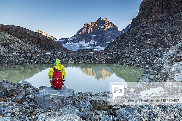 Hiker looks at Piz Roseg from the epiglacial lake next to Fellaria Glacier  Malenco Valley  Sondrio Province  Valtellina  Lombardy  Italy.