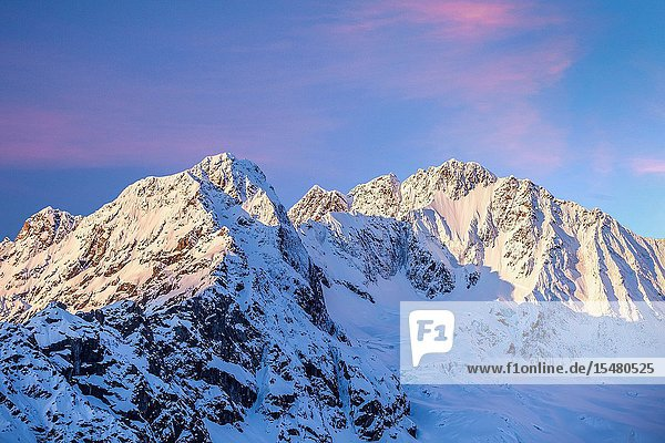The sun is rising on the north wall of Mount Disgrazia and on Ventina Peak after a copious spring snowfall. Photo shot from Alpe dell'Oro. Province of Sondrio. Valmalenco. Valtellina. Lombardy. Italy. Europe.