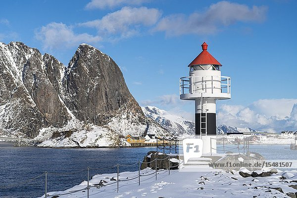 Lighthouse with Festheltinden peak and the village in the background. Reine  Nordland county  Northern Norway region  Norway.