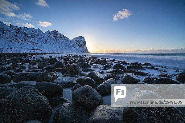 The sun is setting behind Helligberget peak at Unstad Beach. Vestvagoy municipality  Nordland county  Northern Norway  Norway.