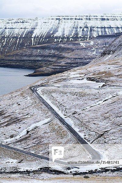 Winding road on mountains towards the ocean  Funningur  Eysturoy island  Faroe Islands  Denmark.