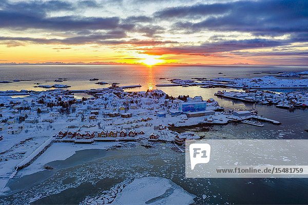 Aerial panoramic of the rising sun over Ballstad and icy sea  Vestvagoy  Lofoten Islands  Norway.