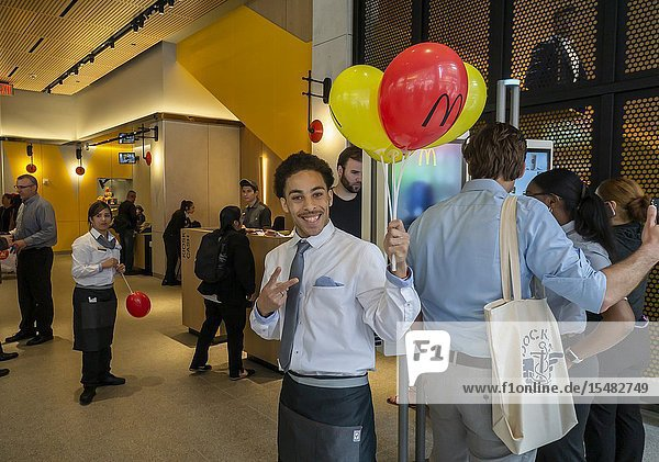 A worker greets customers entering the new McDonaldâ.s in Times Square in New York seen on its grand opening day  Thursday  May 30  2019. The over 11 000 square-foot  three-story store has state-of-the-art kiosk ordering and floor-to-ceiling glass for a view of Times Square for its 170 seats. Although not the largest location in the chain  due to the phenomenal foot traffic at Times Square it is expected to be the busiest. (© Richard B. Levine).
