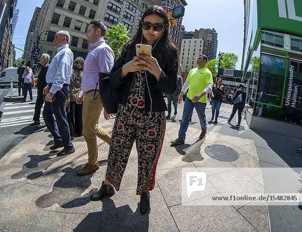 A distracted millennial  engrossed in her smartphone  in New York on Wednesday  May 8  2019. (© Richard B. Levine).