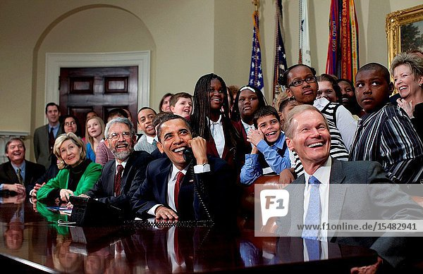 President Barack Obama is joined by members of Congress and school children as he talks March 24  2009  with astronauts on the International Space Station from the Roosevelt Room at the White House. Others seated include Sen. Kay Bailey Hutchison (R-Texas)  left  John Holdren  second eft  Director of the Office of Science and Technology Policy  and Sen. Bill Nelson (D.-Fla)  right  who flew aboard the space shuttle in 1986. (White House PhotoPete Souza)