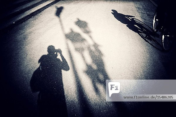 Selfie of the Photographer reflected on the pavement photographing a streetlight. Bucharest  Romania  Europe.
