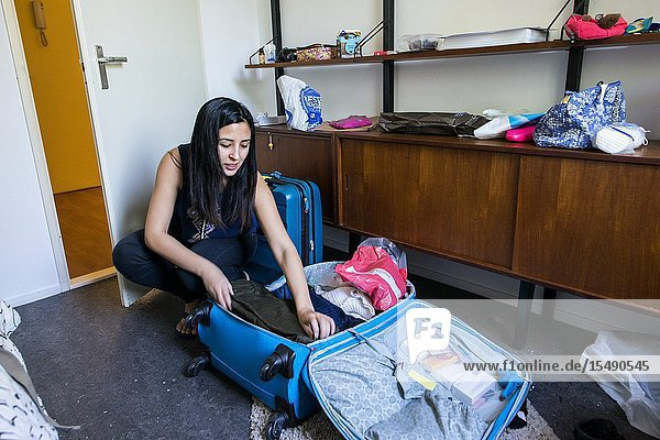 Een jonge  Chileense student pakt haar koffers na een kort verblijf in een Airbnb kamer.
