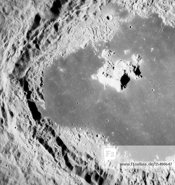 A near vertical view of the crater Tsiolkovsky on the lunar farside  as photographed by the Fairchild metric camera in the Scientific Instrument Module (SIM) bay of the Apollo 15 Command and Service Modules (CSM) in lunar orbit. This view is looking northerly. The coordinates of the crater's central peaks are 128 degrees east longitude and 20 degrees south latitude. The mare area measured from east to west is approximately 145 kilometers (90 statute miles) across. The three-inch mapping camera was one of eight lunar orbital science experiments mounted in the SIM bay.