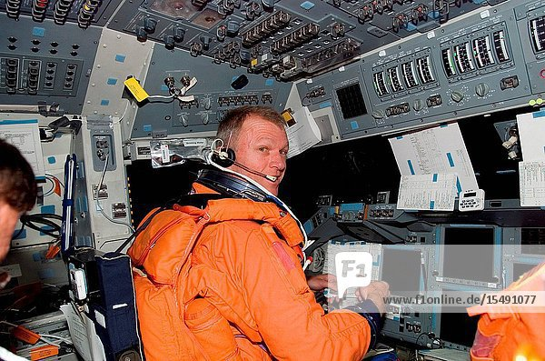 Attired in his shuttle launch and entry suit  astronaut Brent W. Jett  Jr.  STS-115 commander  looks over a procedures checklist as he occupies the commander's station on the flight deck of the Space Shuttle Atlantis prior to entry.