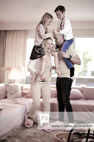 Parents carrying children on shoulders in living room
