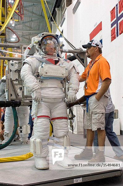NASA astronauts Mike Fossum and Ron Garan (partially obscured)  both STS-124 mission specialists  are about to be submerged in the waters of the Neutral Buoyancy Laboratory (NBL) near Johnson Space Center. Fossum and Garan are attired in training versions of their Extravehicular Mobility Unit (EMU) spacesuits. Divers (out of frame) are in the water to assist the crewmembers in their rehearsal  intended to help prepare them for work on the exterior of the International Space Station.