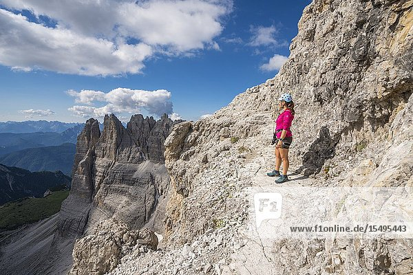 Young woman standing on the via ferrata that leads to the summit of Mount Paterno  in summer. Sesto Dolomites  Trentino Alto Adige  Italy.