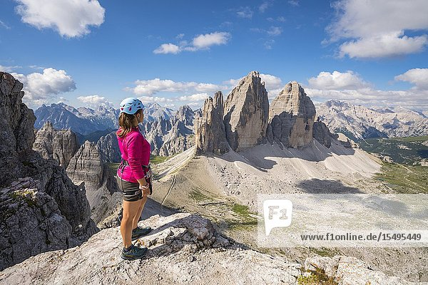 Young woman admiring the landscape around the Three Peaks of Lavaredo from the summit of Mount Paterno  in summer. Sesto Dolomites  Trentino Alto Adige  Italy.