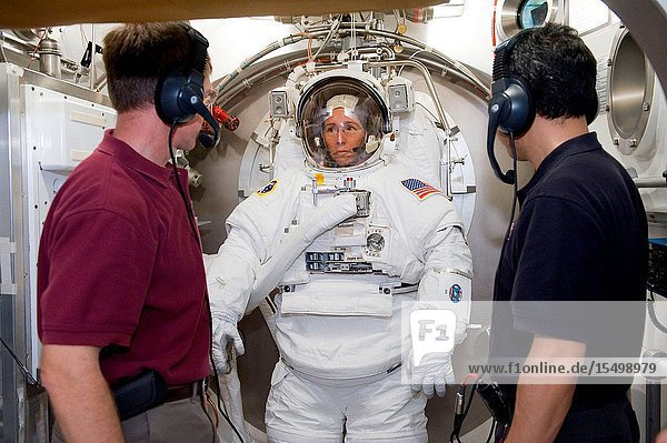 NASA astronaut Sandy Magnus  STS-135 mission specialist  participates in an Extravehicular Mobility Unit (EMU) spacesuit fit check in the Space Station Airlock Test Article (SSATA) in the Crew Systems Laboratory at NASA's Johnson Space Center. NASA astronaut Chris Ferguson (right)  STS-135 commander  and Japan Aerospace Exploration Agency (JAXA) astronaut Satoshi Furukawa  Expedition 2829 flight engineer  assisted Magnus.
