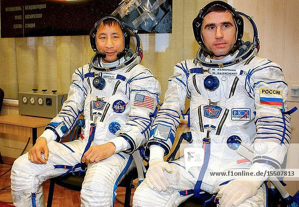 Attired in their Russian Sokol suits  astronaut Edward T. Lu (left)  Expedition Seven NASA ISS science officer and flight engineer  and cosmonaut Yuri I. Malenchenko  mission commander  await to participate in a leak check  Soyuz inspection  and seat liner check in the Soyuz Integration Facility at the Baikonur Cosmodrome in Kazakhstan. Malenchenko represents Rosaviakosmos.