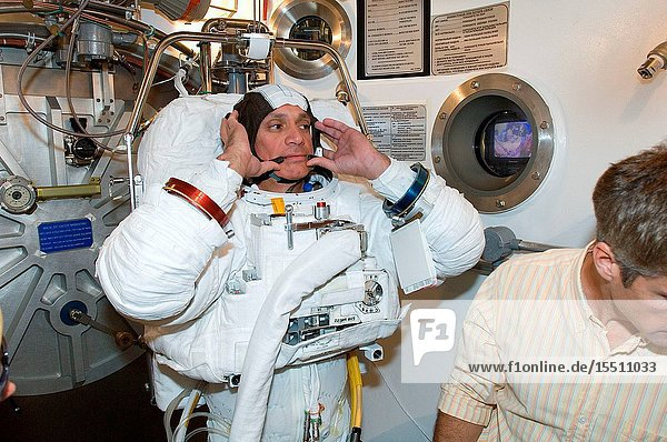 Astronaut John D. (Danny) Olivas  STS-117 mission specialist  participates in an Extravehicular Mobility Unit (EMU) spacesuit fit check in the Space Station Airlock Test Article (SSATA) in the Crew Systems Laboratory at the Johnson Space Center. Astronaut Steven R. Swanson (partially out of frame)  mission specialist  assisted Olivas.