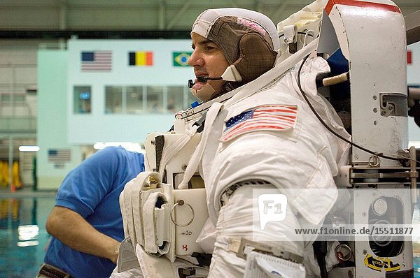 Astronaut Rex J. Walheim  STS-122 mission specialist  dons a training version of the Extravehicular Mobility Unit (EMU) spacesuit in preparation for a training session in the waters of the Neutral Buoyancy Laboratory (NBL) near Johnson Space Center.