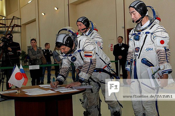 At the Gagarin Cosmonaut Training Center in Star City  Russia  Expedition 4243 backup Soyuz Commander Oleg Kononenko of Roscosmos signs in for the first of two days of qualification exams October 30 as his crewmates  Kjell Lindgren of NASA (left) and Kimiya Yui of the Japan Aerospace Exploration Agency look on. They are the backups to the prime crew