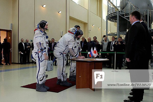 At the Gagarin Cosmonaut Training Center in Star City  Russia  Expedition 46-47 backup crewmember Anatoly Ivanishin of the Russian Federal Space Agency (Roscosmos) signs in Nov. 19 for the start of qualification exams as his crewmates  Kate Rubins of NASA (left) and Takuya Onishi of the Japan Aerospace Exploration Agency (right  behind Ivanishin) look on. They are the backups to the prime crewmembers  Yuri Malenchenko of Roscosmos  Tim Kopra of NASA and Tim Peake of the European Space Agency  who will launch Dec. 15 in the Soyuz TMA-19M spacecraft from the Baikonur Cosmodrome in Kazakhstan for a six-month mission on the International Space Station.