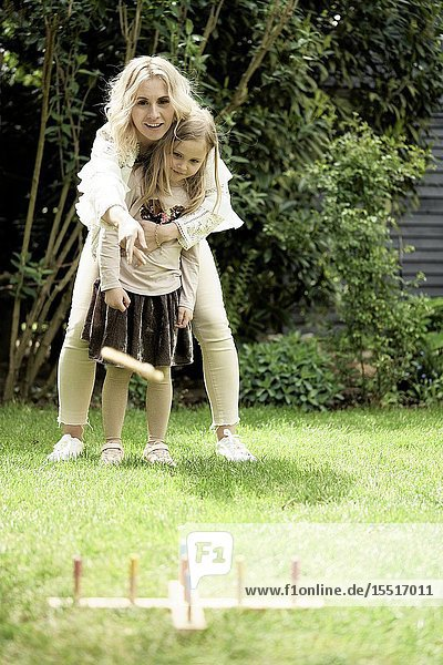 Mother and daughter playing game in garden.
