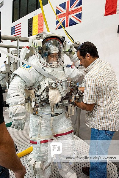NASA astronaut Sunita Williams  Expedition 32 flight engineer and Expedition 33 commander  dons a training version of her Extravehicular Mobility Unit (EMU) spacesuit in preparation for a spacewalk training session in the waters of the Neutral Buoyancy Laboratory (NBL) near NASA's Johnson Space Center. NASA astronaut Joe Acaba  Expedition 3132 flight engineer  assisted Williams.