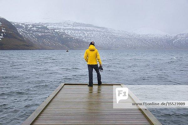 Photographer is looking the fjord at the Faroe Islands (Hosvik  Streymoy island  Faroe Islands  Denmark) (MR).