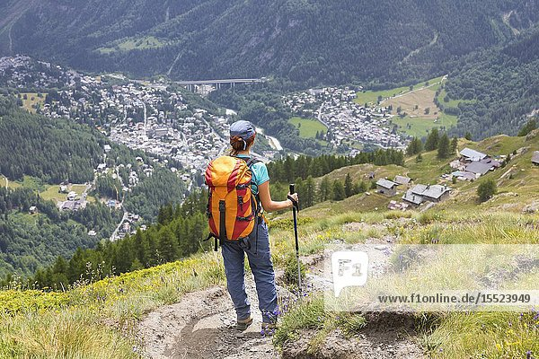 A girl is watching the village of Courmayeur from the top during the Mont Blanc hiking tours (Mont de la Saxe  Ferret Valley  Courmayeur  Aosta province  Aosta Valley  Italy  Europe) (MR).